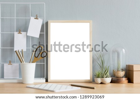Home interior of creative desk with mock up photo frame on the brown wooden table with office accesories, tillandsia in design pots, notebook and notes. Grey walls. Minimal concept of mockup. #1289923069