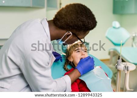 Regular dentist visit. Caries cure. Little girl visiting dentist surgeon in hospital #1289943325