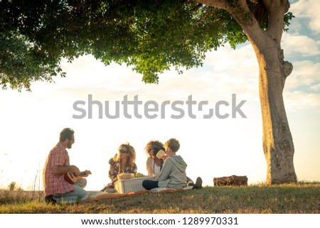 Friends eat on meadow happy young blond curly woman with plaid shirt plays guitar brunette friend headband smiles singing man with beard drinks bottle of beer and blond child looks amused under tree