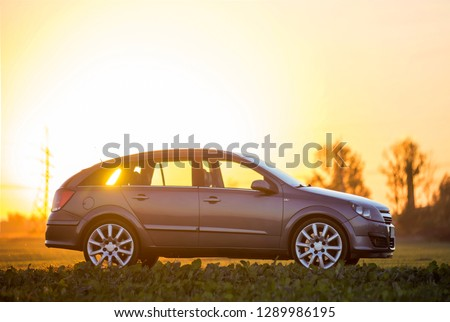 Modified image of a fictional non existent car. Gray car parked in countryside on blurred rural landscape and orange sky at sunset copy space background. Transportation, traveling concept. #1289986195
