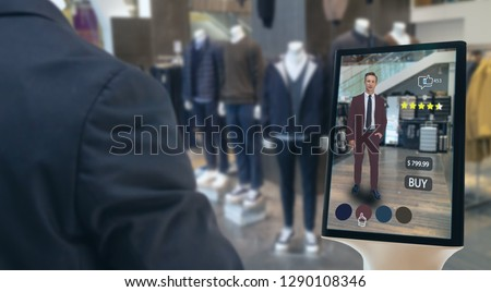 iot smart retail futuristic technology concept, happy man try to use smart display with virtual or augmented reality  in the shop or retail to choose select ,buy cloths and give a rating of products  #1290108346