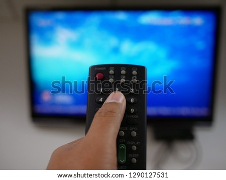 closeup of hand with the remote control television and presses the button.  #1290127531