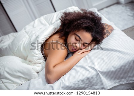 Dark-skinned woman resting. Curly short-haired lady putting head down on connected hands during deep sleep #1290154810