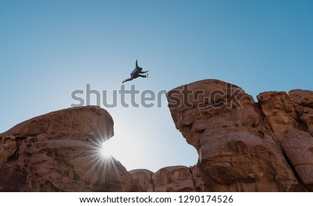 Challenge, risk and freedom concept. Silhouette a man jumping over precipice crossing cliff #1290174526
