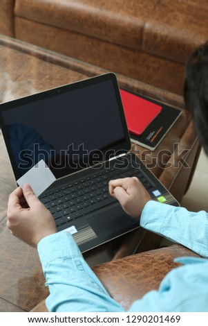Man is holding card in hand with laptop.