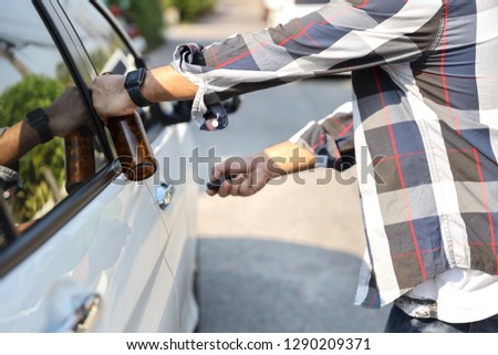 drunk man try opening vehicle with car key while holding alcohol bottle in another hand (drink not drive concept) #1290209371