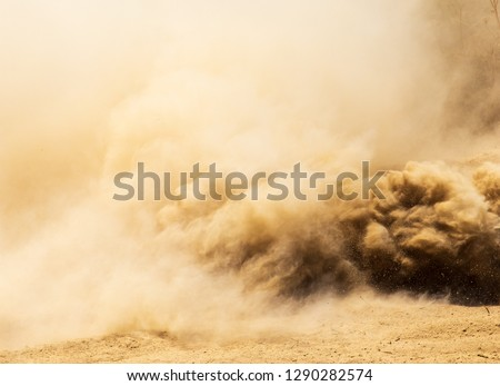 A cloud of dust from cars on nature as a background Royalty-Free Stock Photo #1290282574