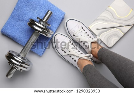Legs of young sporty woman, dumbbell, towel and notebook on white background #1290323950