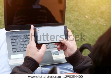 Man is using smartphone with laptop.