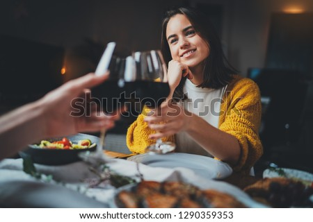 Romantic couple dating at night in restaurant, cozy atmosphere, beautiful young couple making cheers with glasses of red wine during romantic dinner, Sweet Couple Date Dinner #1290359353