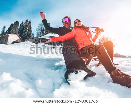 Happy influencers couple having fun with wood vintage sledding on snow high mountains - Young crazy people enoying winter vacation - Travel and holiday concept - Focus on faces #1290381766