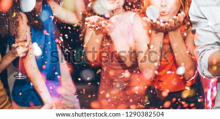 Happy friends making carnival party throwing confetti - Young people celebrating on weekend night - Entertainment, fun, nightlife and fest concept - Focus on center girl hands Royalty-Free Stock Photo #1290382504