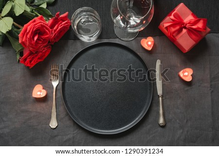 Valentine's day or birthday romantic dinner. Elegance table setting with red rose on black linen tablecloth. #1290391234