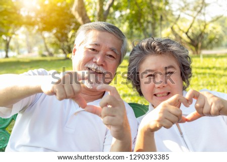 Grandma and grandpa or grandparents make symbol of love by using hands and fingers for making hearts. Lovely older couple or senior people love each other for long time. They give love to their family #1290393385
