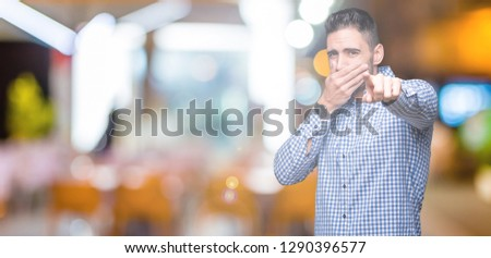 Young handsome man over isolated background Laughing of you, pointing to the camera with finger hand over mouth, shame expression #1290396577