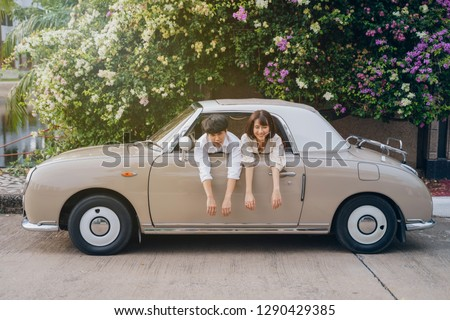 Portrait of hipster couple with classic car. Love on road trip concept. #1290429385