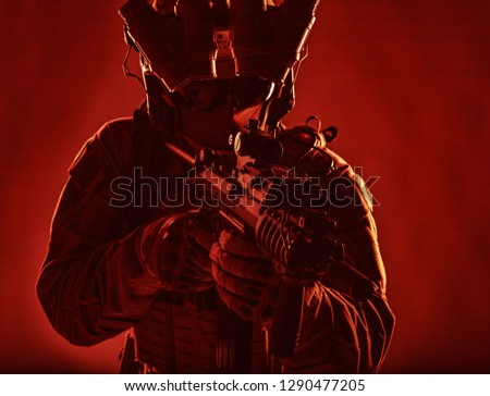 Special operations forces soldier, counter terrorism assault team fighter with night vision device on helmet and red dot laser sight on service rifle, low key studio shoot silhouette with backlight #1290477205
