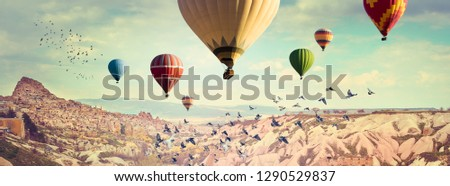 Hot Air balloons flying above the Pigeon`s Valley near the ancient cave town Uchisar. Wide panorama of Cappadocia with multicolored balloons over colorful mountain landscape. #1290529837