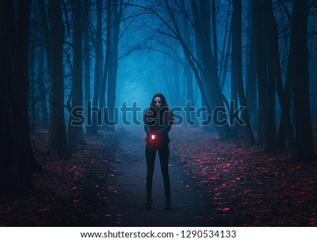 Background for wallpaper. Girl stands on the road in the night forest and shines a lantern. Mystical Strange forest in a fog with red leaves. Background mystic atmosphere. Dark mysterious park #1290534133