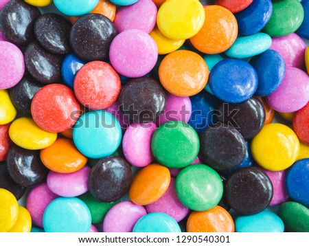 Top view of colorful button-shaped chocolates or candy-coated chocolate. background #1290540301