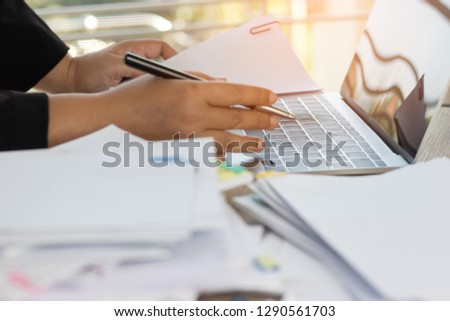 Teacher hand holding pen for checking students homework assignment on table office. Paper documents stacked in archive with colorful paperclip. Report papers stacks. Business and education concept. #1290561703
