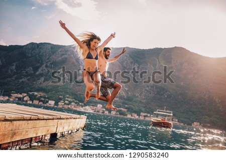 Young couple jumping from a pier into the water #1290583240