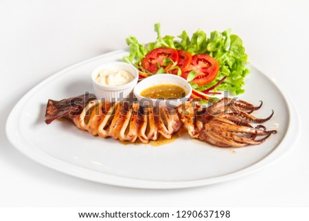 Grilled squid caramary  on whire plate served with thai spicy sauce, mayonnaise  and vegetables on white background