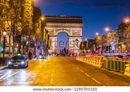 PARIS FRANCE - OCTOBER 1, 2018: Empty road leading to the Arc de Triomphe in Paris, France. Golden lightsources hitting the ground reflects on the entire street. Shot at night #1290701320