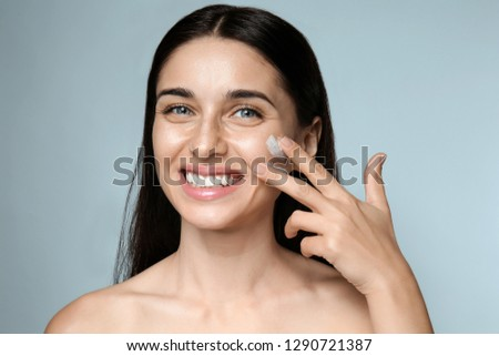 Portrait of beautiful young woman applying facial cream on color background #1290721387