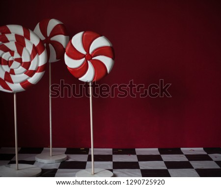 red and white stripped candies on red background.  lollipop standing on chessboard. copy space