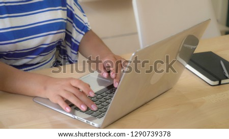 lady typing on computer sitting at the office desk working with pc. #1290739378