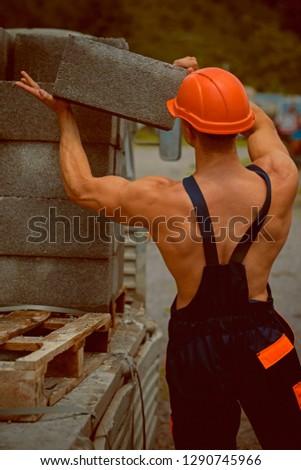 Builder concept. Builder unload truck. Builder in working uniform. Builder carry bricks. Safety comes first. #1290745966
