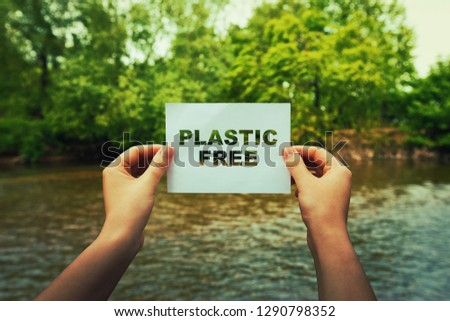 Woman hands holding a paper sheet with plastic free text in the middle of the nature near a flowing river and green forest. Ecology concept, recycle symbol, zone with no plastic. Royalty-Free Stock Photo #1290798352
