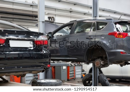 Automobile workshop. Cars standing on the hydraulic lift for repair and replacement wheel. Modern service. #1290954517
