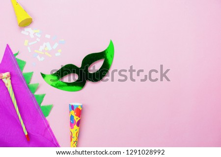 Table top view aerial image of beautiful colorful decorations Mardi Gras or carnival festival background.Flat lay accessory object the mask & hat with decor confetti birthday on modern pink paper.