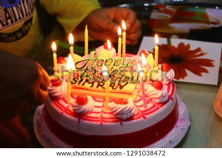 A beautiful pic of cake with candles and a waffle in which simran written on it