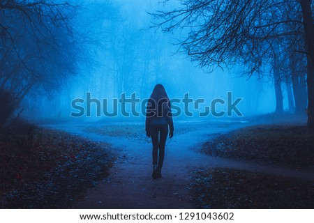 Girl goes on the road in a mysterious forest. Background for wallpaper. Strange forest in a fog with red leaves. Mystic atmosphere. Dark scary park. Paranormal another world. #1291043602