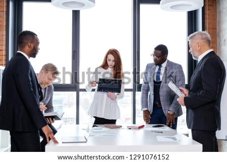Business team of ethnic people working in the office standing at the table brainstorming #1291076152