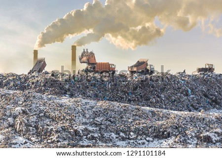 Dump trucks unloading garbage over vast landfill. Smoking industrial stacks on background. Environmental pollution. Outdated method of waste disposal. Survival of times past #1291101184