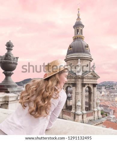 Good-looking girl in jeans and elegant hat posing under pink sky. Outdoor photo of cute young woman in european city. Budapest view. Girl looking at the city.