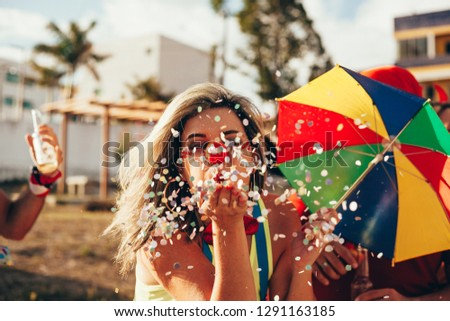 Brazilian Carnival. Young woman in costume enjoying the carnival party blowing confetti #1291163185
