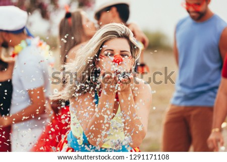 Brazilian Carnival. Young woman in costume enjoying the carnival party blowing confetti #1291171108