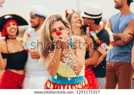 Brazilian Carnival. Young woman in costume enjoying the carnival party blowing confetti #1291171357