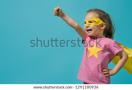 Little child playing superhero. Kid on the background of bright blue wall. Girl power concept. Yellow, pink and  turquoise colors. #1291180936