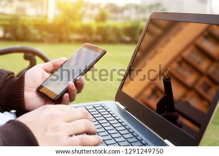 Man is holding smartphone in hand with laptop.