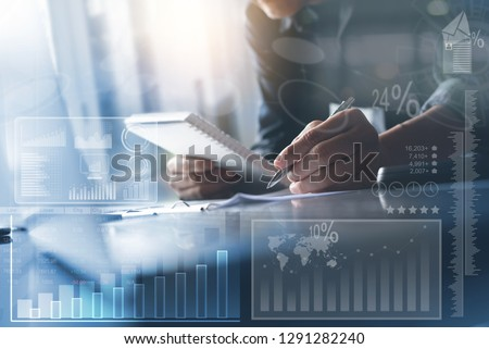 Business strategy analysis concept. Asian businessman working on laptop computer at modern office with financial graph diagram, business data computer dashboard on virtual screen #1291282240