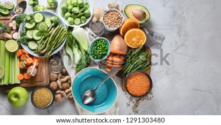 Fresh healthy vegan and vegetarian food on grey background. Diet, detox, clean eating concept. Top view. Panorama, banner  with copy space