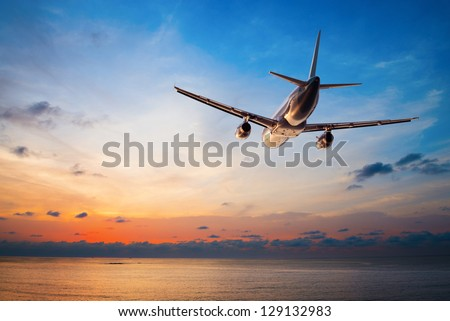 Airplane flying above tropical sea at sunset Royalty-Free Stock Photo #129132983