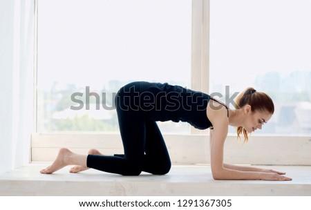 A woman is kneeling on a windowsill yoga asana                               #1291367305