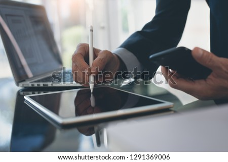 Electronic signature, Business and  technology concept. Businessman working on digital tablet signing contract with digital pen, holding mobile smart phone with laptop computer and business document